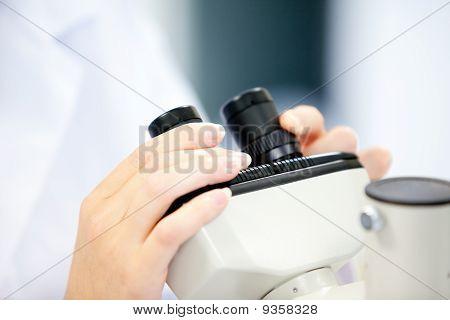 Primer plano de un científico mujer mirando a través de un microscopio