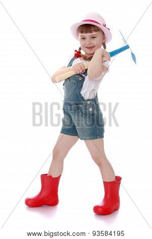 Cheerful girl gardener in rubber boots