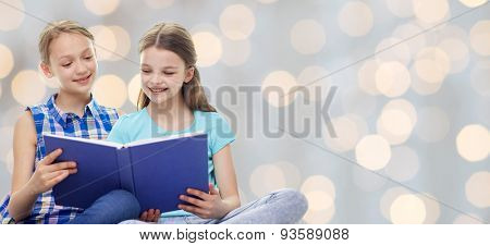 people, children, friends, literature and friendship concept - two happy girls sitting and reading book over holidays lights background