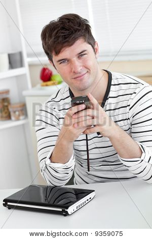 Smiling Man Sending A Text Message With His Cellphone In Front Of His Laptop In The Kitchen