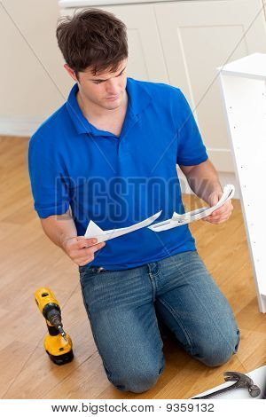 Concentrated Young Man Reading The Instructions To Assemble Furniture In The Kitchen