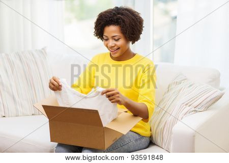 people, delivery, commerce, shipping and postal service concept - happy african american young woman taking clothes out of cardboard box or parcel at home