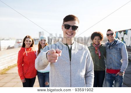 people, friendship and international concept - happy young man or teenage boy pointing finger to you in front of his friends on city street