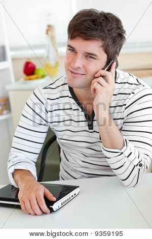 Delighted Man Talking On Phone Using His Laptop In The Kitchen