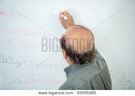 Senior chemistry professor giving a lecture in front of classroom