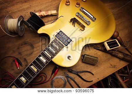 Electric guitar repair. Vintage electric guitar on a guitar repair work shop. Single cutaway solid body guitar, gold color. shallow depth of view, intentionally shot with low key shadows.