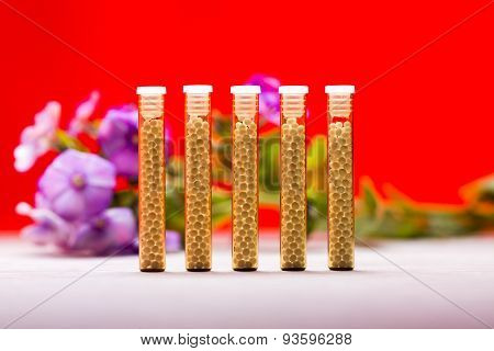 Five Small Glass Tubes With Homeopathy Globules, Red Background And Flowers