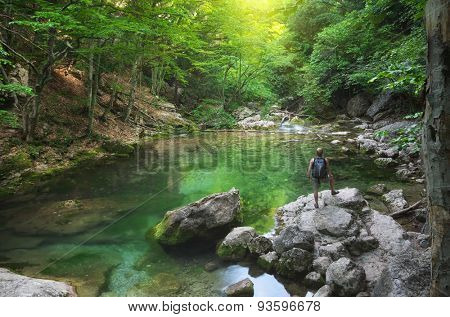 Man into canyon. Spring lake and green forest. Nature composition.