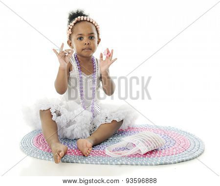 An adorable little girl sitting on a rug in her white petticoat.  She's adorned with strands of beads and holds up a bracelet and rings.  On a white background with space on the right for your text.