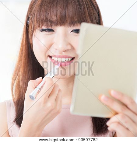 Portrait of attractive Asian girl putting lipstick on lips. Young woman living lifestyle.