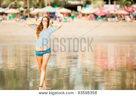 Beautifil young woman walking along the beach at sunset enjoing summer vacation