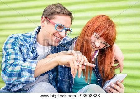 Happy Young Couple Having Fun With Smartphone At Vintage Grunge Location - Concept Of Friendship