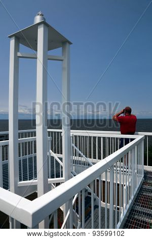 Man Looking Through Binoculars At Top Of Harbor Light