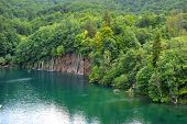 foto of emerald  - picturesque emerald lake in forest high in mountains with waterfalls - JPG