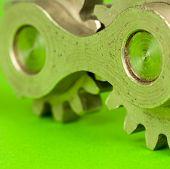 stock photo of kinetic  - Metal shiny cogwheel element shot on green paper background as closeup image - JPG