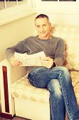 picture of only mature adults  - Mature man relaxing with newspaper on the sofa - JPG