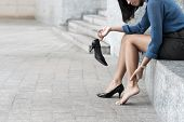 foto of ankle shoes  - Woman with shoe sitting outdoors and massaging ankle - JPG