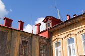 picture of red roof  - Red painted roofing and chimney stacks against a blue sky - JPG