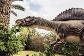 picture of dead plant  - ancient extinct dinosaur spinosaurus on a background of plants - JPG