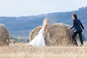 image of hay bale  - Young married couple kissing on a hay bale - JPG