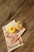 pic of conch  - Yellow rubber duck conch with money of Thai Bath - JPG