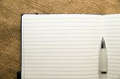 stock photo of memento  - Opened notebook with a blank sheet and pen on the old tissue - JPG