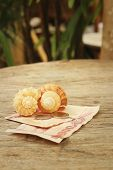 foto of conch  - Conch with money of Thai Bath on background of wooden - JPG