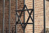image of old stone fence  - Star of David on metal fence of Old Synagogue in jewish district of Cracow  - JPG