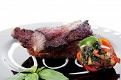 foto of braai  - fresh red beef meat steak barbecue garnished vegetable salad sweet potato and basil on black plate isolated over white background - JPG