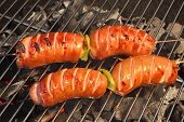 image of grilled sausage  - Four Tasty Sausages On The Hot Barbecue Charcoal Grill Close - JPG