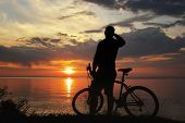 foto of dirt-bike  - silhouette of a man with a mountain bike on the river bank at sunset - JPG