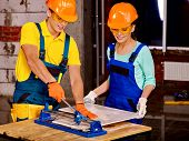 foto of millwright  - Happy group people of two person builder cutting ceramic tile - JPG