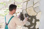 pic of mason  - Mason putting decorative natural stones on a wall - JPG