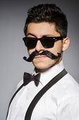 image of moustache  - Young man with false moustache isolated on gray - JPG