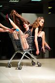 foto of trolley  - Two young sensual playful fashionable girls in dresses with shopping trolley indoor on store backdrop vertical picture - JPG