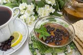 picture of chokeberry  - Chokeberry tea in a porcelain cup on a flower decorated table - JPG