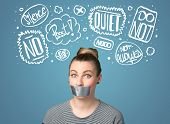 image of taboo  - Young woman with taped mouth and white drawn thought clouds around her head - JPG