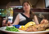 foto of lobster tail  - Closeup of a steak and lobster dish on a white plate in front of a blurred woman holding silverware sitting in a booth in a restaurant - JPG