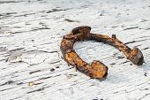 picture of horseshoe  - Rusty horseshoe on an old white painted surface - JPG