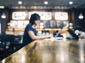 stock photo of cafe  - Blurred Woman working with laptop on table in cafe restaurant background - JPG