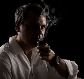 foto of tobacco-pipe  - Portrait of pipe smoker man smoking vintage tobacco pipe on black background