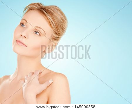 beauty, people and bodycare concept - beautiful young woman face and hands over blue background