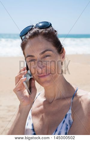 Woman At Beach Talking On Mobile Phone Looking