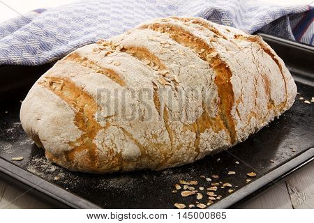 country house style baked loaf with oatmeal on black baking tray