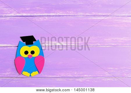Colored cardboard owl isolated on a lilac wooden background with empty place for text. Bright owl made of colored cardboard. School background