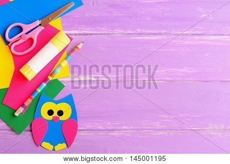 Cute owl decor, stationery. Coloured cardboard owl decor, scissors, glue stick, pencil, colored cardboard sheets on lilac wooden background with blank space for text. Children background. Top view
