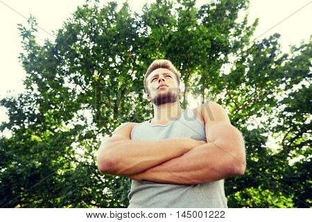fitness, sport, people and healthy lifestyle concept - sporty young man with crossed arms at summer park