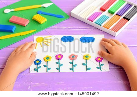 Child shows a card with plasticine flowers, sun and clouds. Supplies for children art crafts on a wooden table. Modeling clay crafts idea for kids. Activity in kindergarten and at home