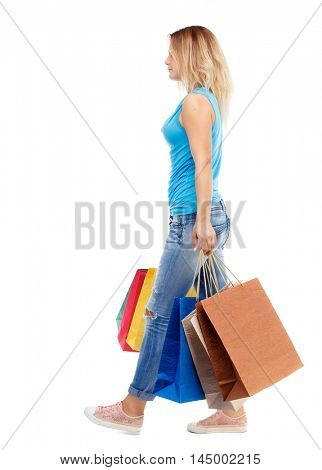 side view of going woman with shopping bags .Isolated over white background. The blonde in a blue shirt and jeans walks past with colorful packages.