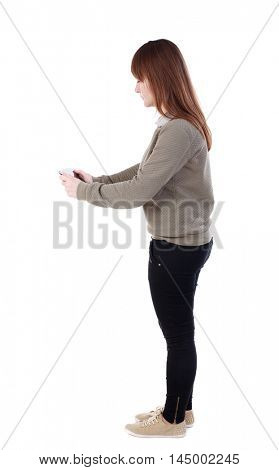 back view of standing young beautiful woman using a mobile phone. girl watching. girl in a gray jacket playing games on the phone standing sideways.